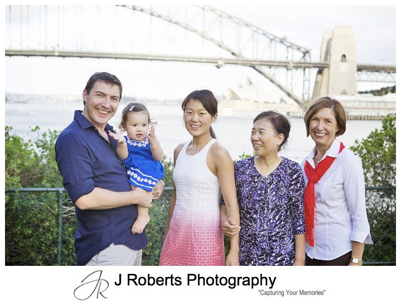 Baby girl with her parents and grandmothers and sydney harbour in the background - sydney family portrait photography